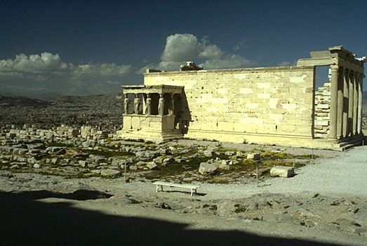 View of the south and east sides of the Erechtheion. The blue limestone foundations of the Old Athena Temple (built c. 510-500 BC and destroyed by the Persians in 480 BC) are visible in the foreground. - Photo taken in 1989, from the southeast (from the northern pteron of the Parthenon).