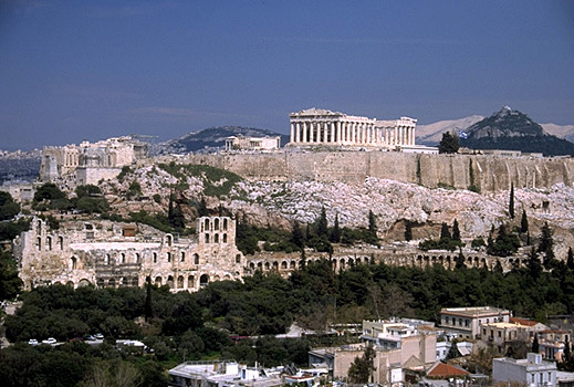 View of the Acropolis and the South Slope from the southwest (from near the Philopappos Monument). - In the background to the right of the Parthenon are Mt. Lykabettos and Mt. Penteli. Photo taken in 1998. by Kevin T. Glowacki and Nancy L. Klein