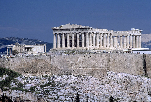 View of the Erechtheion, the Parthenon, and the south wall of the Acropolis. - View from the southwest (from near the Philopappos Monument). In the background to the right of the Parthenon are Mt. Lykabettos and Mt. Penteli. Photo taken in 1998. by Kevin T. Glowacki and Nancy L. Klein