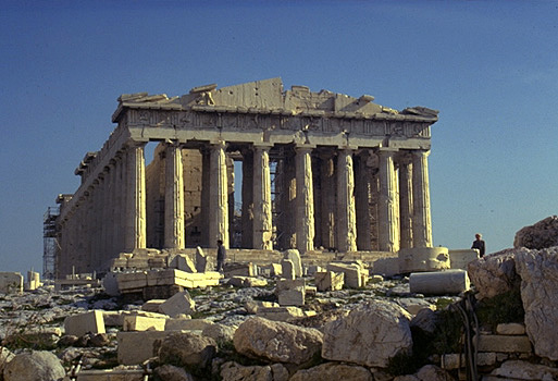 The Parthenon, western facade. - View from east of the Temple of Athena Nike. The large limestone boulders in the forground are part of the Mycenaean fortification wall.