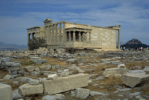 General view of the Erechtheion from the southwest, showing the North Porch (at left), the Olive Tree of Athena (modern replacement!), and the Carytatid Porch. - Note the modern (white) blocks of Pentelic marble which have been used in the reconstruction of the building. The blue limestone foundations of the Old Athena Temple (built c. 510-500 BC and destroyed by the Persians in 480 BC) are visible south of the E