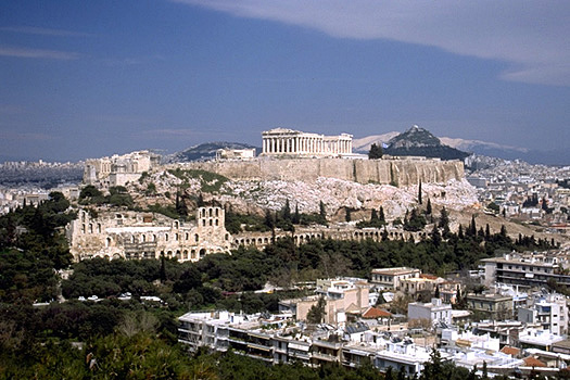 View of the Acropolis and the South Slope from the southwest (from near the Philopappos Monument). - In the background to the right of the Parthenon are Mt. Lykabettos and Mt. Penteli. Photo taken in 1998.
